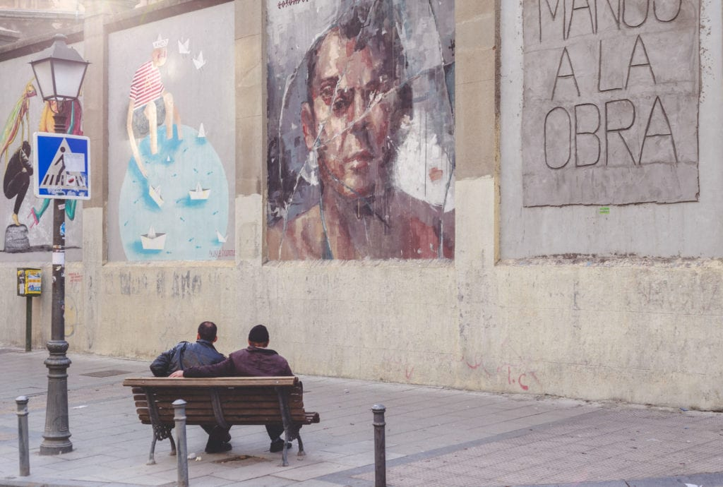 two man sitting on the bench and looking at the graffiti