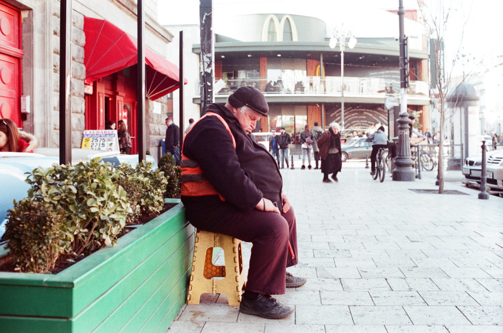 A man in the street sleeping on a chair