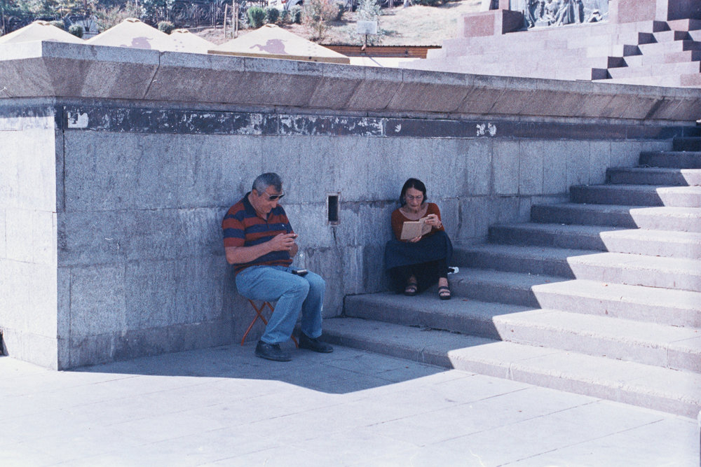 man and a woman sitting in the shadow reading a book